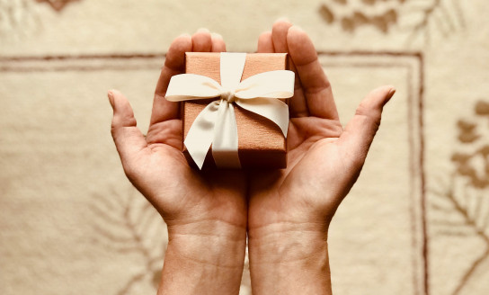 person s holds brown gift box 842876