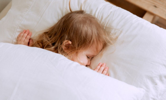 photo of child laying on bed 3933069